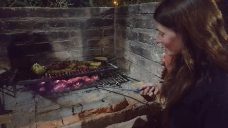 Lali haciendo asado en parrilla de cabaña alquilada en La Rioja