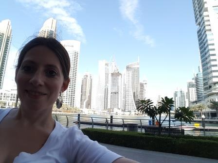 Lali almorzando en restaurant con la Marina Dubai de fondo