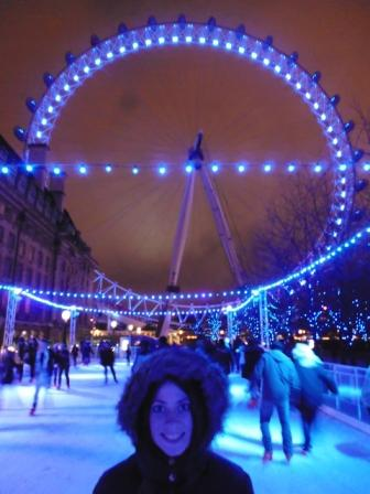 Lali patinando en pista de patinaje sobre hielo con London Eye de fondo