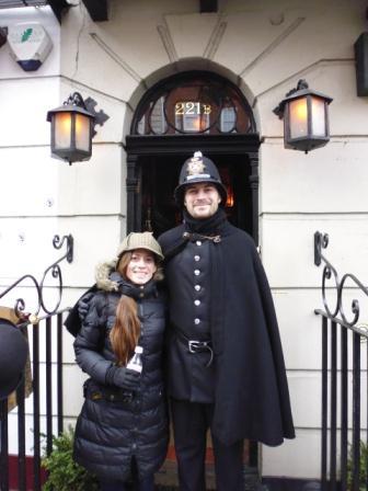Lali con el guardia y vistiendo el sombrero típico en la puerta del Museo de Sherlock Holmes