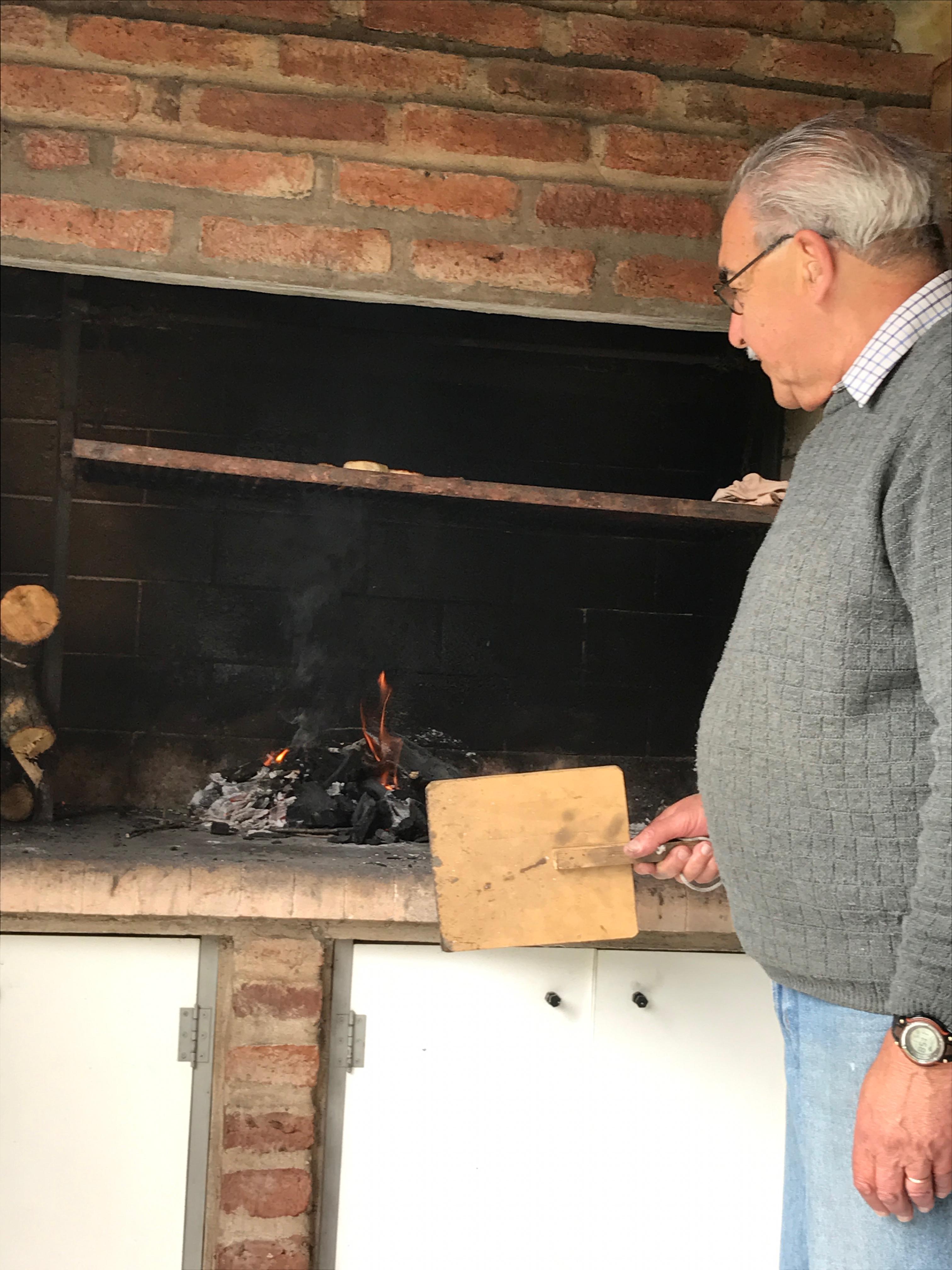 Papá de Lolo avivando el fuego hasta que todos los carboncitos estén encendidos.